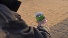 Close-up homeless beggar`s hand with paper cup. Close-up homeless beggar male`s hand holding paper cup. Man begging for money on the street, people`s legs stock footage