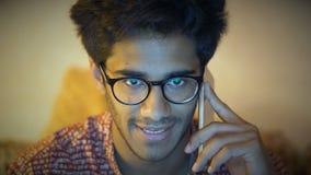 Close-up, homem indiano bonito nos vidros que fala no telefone vídeos de arquivo