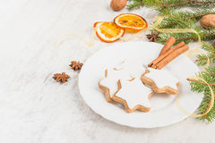 Close up of homemade butter nuts star shaped cookies with icing, pine, orange slices,cinnamon, anise, walnuts and golden ribbon ov Royalty Free Stock Image
