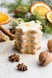 Close up of homemade butter nuts star shaped cookies with icing, pine, orange slices,cinnamon, anise, walnuts and golden ribbon ov Stock Photography