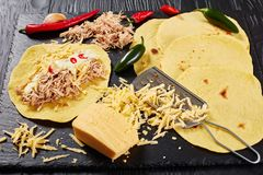 Close-up of tasty homemade corn tortillas. Close-up of homemade corn tortillas with shredded meat, sauce, grated cheese and pieces of chili on black stone board Stock Image
