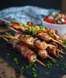 Close-up of homemade honey and beer BBQ chicken skewers with fresh parsley stock photo