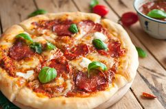 Close-up of homemade rustic pizza with salami, mozzarella and fresh basil on top stock images