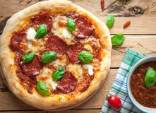 Close-up of homemade rustic pizza with salami, mozzarella and fresh basil, top view. Close-up of homemade rustic pizza with salami, mozzarella and fresh basil on royalty free stock photos