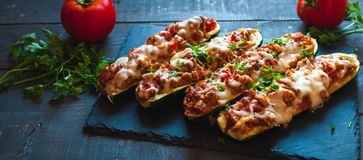 Close-up of stuffed zucchini boats with ground beef, spicy tomato sauce, cheese and fresh parsley, on dark background. Close-up of homemade stuffed zucchini stock photo