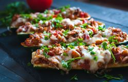 Close-up of stuffed zucchini boats with ground beef, spicy tomato sauce, cheese and fresh parsley, on dark background. Close-up of homemade stuffed zucchini stock image