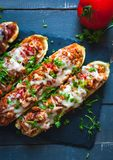 Close-up of stuffed zucchini boats with ground beef, spicy tomato sauce, cheese and fresh parsley, on dark background, top view. Close-up of homemade stuffed stock photos