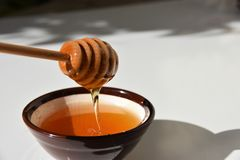 Honey dipper dipped in honey and then lifted up. Close up for honey dipper lifted up from honey bowl , showing its transparent orangish - yellowish colour and Royalty Free Stock Photography