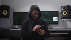Close up of a hooded hacker making cyber attack on bank network with the help of smartphone in his hands. Man in black stock footage