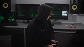 Close up of hooded hacker making cyberattack on network with the help of tablet in his hands. Man is typing fast on his stock video footage