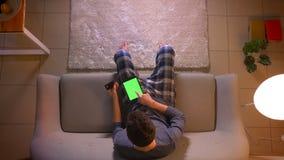 Close-up hoogste spruit van de jonge mens die online met creditcard winkelen die de tablet met het groene scherm gebruiken terwij stock videobeelden