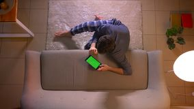 Close-up hoogste spruit van de jonge mens die op een reclame letten de tablet met het groene scherm terwijl binnen het zitten op  stock videobeelden