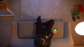Close-up hoogste spruit van de jonge vrij vrouwelijke het letten op zitting van TV op de laag die app op de telefoon met het groe stock videobeelden