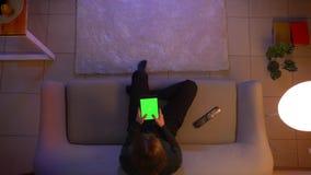 Close-up hoogste spruit van het jonge vrij vrouwelijke texting op de tablet met het groene scherm die op TV letten en op zitten stock video