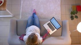 Close-up hoogste spruit van het jonge zwangere vrouwelijke mamma ver werken gebruikend laptop terwijl binnen het zitten op de laa stock footage