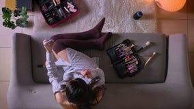 Close-up hoogste spruit van jong aantrekkelijk wijfje die een make-up toepassen gebruikend een zitting van de telefoonspiegel op  stock video