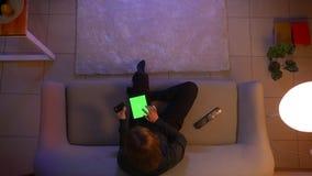 Close-up hoogste spruit van jong mooi wijfje die online op de tablet met het groene op TV letten en scherm winkelen die zitten stock footage