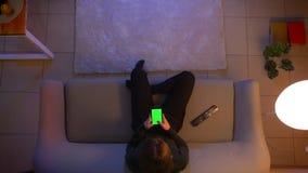 Close-up hoogste spruit van jong vrij vrouwelijk overseinen op de telefoon met het groene scherm voor TV en zitting op stock footage