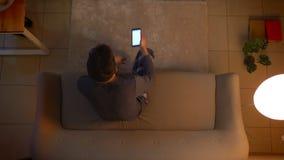 Close-up hoogste spruit van jonge mannelijke zitting neer op de laag en het aanzetten van TV die app op de telefoon gebruiken als stock footage