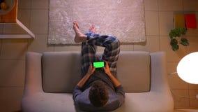 Close-up hoogste spruit van jonge mens het spelen videospelletjes op de telefoon met het groene scherm terwijl het zitten op de l stock videobeelden