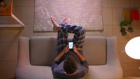 Close-up hoogste spruit van jonge mens het texting op de telefoon terwijl het zitten op de laag binnen bij comfortabel huis stock footage