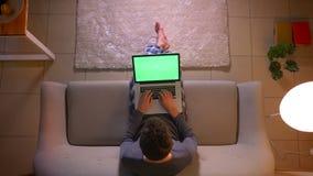 Close-up hoogste spruit van jonge mensenoverseinen op laptop met het groene scherm terwijl het zitten op de laag binnen bij comfo stock footage