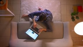 Close-up hoogste spruit van jonge zakenman die een diagram creëren die aan laptop werken terwijl het zitten op de vloer binnen bi stock footage