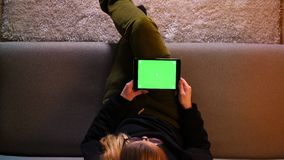 Close-up hoogste spruit van mooi meisje die de tablet met het groene scherm gebruiken een tijdje die op de bank binnen in comfort stock video