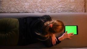 Close-up hoogste spruit van mooi meisje die de tablet met het groene scherm gebruiken terwijl het liggen op de bank binnen in een stock videobeelden