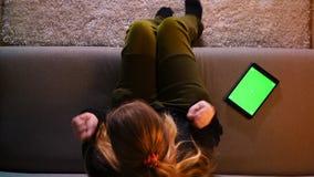 Close-up hoogste spruit van mooi meisjesoverseinen op de tablet met het groene scherm die opgewekt terwijl het zitten op de bank  stock videobeelden