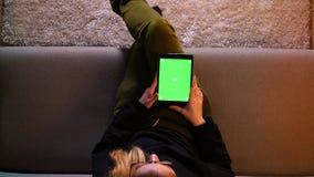 Close-up hoogste spruit van mooi meisjesoverseinen op de tablet met het groene scherm terwijl het zitten op de bank binnen in com stock footage