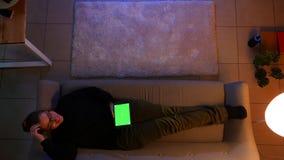 Close-up hoogste spruit van mooi wijfje die de tablet met het groene scherm gebruiken terwijl het liggen op de bank binnen in com stock footage