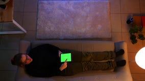 Close-up hoogste spruit van mooi wijfje die de tablet met het groene scherm gebruiken terwijl het liggen op de bank binnen in com stock videobeelden