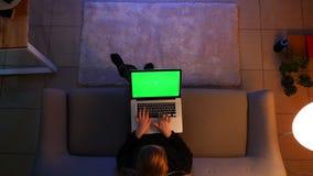 Close-up hoogste spruit van mooi wijfje die laptop met het groene scherm met behulp van terwijl het zitten op de bank binnen in c stock video