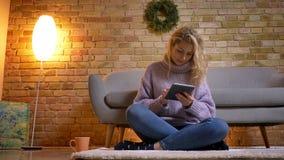 Close-up hoogste spruit van volwassen Kaukasisch blondewijfje die de tablet gebruiken terwijl het zitten op de vloer binnen in co stock video