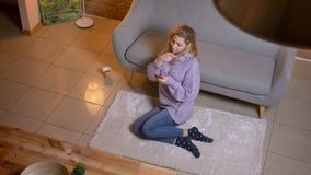 Close-up hoogste spruit van volwassen Kaukasisch blondewijfje die de telefoon met behulp van terwijl het zitten op de vloer en he stock videobeelden