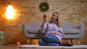 Close-up hoogste spruit van volwassen Kaukasisch blondewijfje die selfies op cellphone nemen terwijl binnen het aanwezig zijn op  stock videobeelden