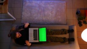 Close-up hoogste spruit van vrij het vrouwelijke texting op laptop met het groene scherm die opgewekt terwijl het liggen op de ba stock videobeelden
