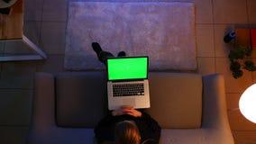 Close-up hoogste spruit van vrij het vrouwelijke typen op laptop met het groene scherm terwijl het zitten op de bank binnen in co stock footage