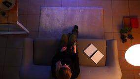 Close-up hoogste spruit van vrij vrouwelijke het letten op TV terwijl het zitten op de laag binnen in een comfortabele flat met w stock footage