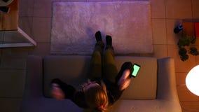 Close-up hoogste spruit van vrij vrouwelijke tiener die op TV letten die de telefoon met behulp van die opgewekt terwijl het zitt stock videobeelden