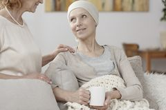 Hopeful woman suffering from cancer. Close-up of a hopeful women suffering from cancer and her friend comforting her Stock Photo