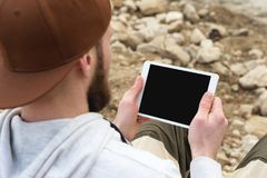 Close-up of a horde in a brown cap in the open air holds a white tablet pc in his hands. A bearded man looks at the stock photos