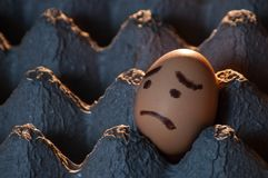 Close-up of a sad-faced egg in an egg tray. Close-up horizontal image of an egg with a sad face painted on it Royalty Free Stock Photo