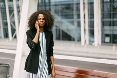 Close-up horizontal portrait of the beautiful serious afro-american girl talking via the mobile phone. Royalty Free Stock Image