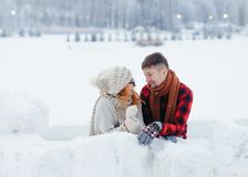 Close-up horizontal portrait of the happy beautiful couple funnily talking while building the snowman in the countryside Royalty Free Stock Images