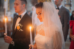 The close-up horizontal portrait of the newlyweds holding candles during the wedding ceremony. Stock Photography