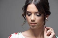 Close up horizontal portrait of sad pensive beautiful model girl touching hair lock looking down Royalty Free Stock Photos