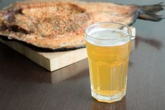 Close up horizontal view of smoked fish fillets with seasoning on wooden serving board and glass of cold beer next to it royalty free stock photography