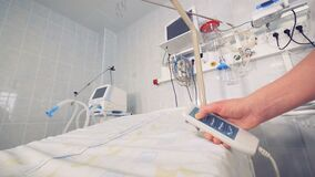 Close up of a hospital bed getting lifted by remote control in doctor`s hand. 4K stock footage